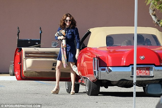 The actress shoots a driving scene as she gets out of a convertible