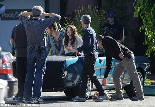 The crew prepare the scene as the stars sit in a convertible car